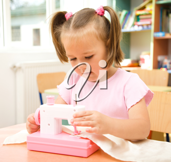 Royalty Free Photo of a Little Girl With a Toy Sewing Machine