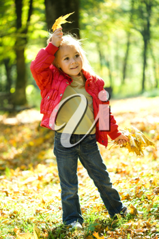 Royalty Free Photo of a Little Girl Playing in Autumn Leaves