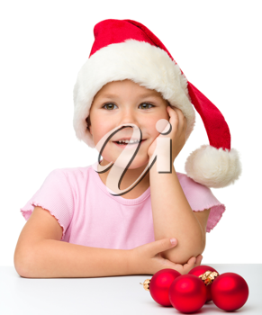 Royalty Free Photo of a Girl in a Santa Hat and Ornaments