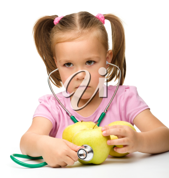 Royalty Free Photo of a Girl Using a Stethoscope on an Apple