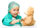 Royalty Free Photo of a Little Girl in Doctor's Scrubs Listening to Her Teddy Bear's Heart