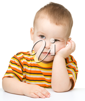 Portrait of a cute and pensive little boy, isolated over white