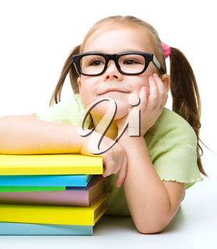Cute little girl with books while wearing glasses, isolated over white