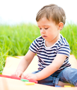 Little boy is playing with toys while sitting on green grass outdoors