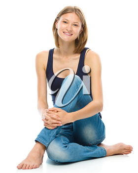 Young happy woman is sitting on the floor, isolated over white