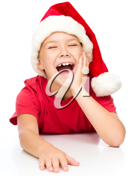 Little girl in santa hat is laughing supporting her head with hand and closed eyes, isolated over white