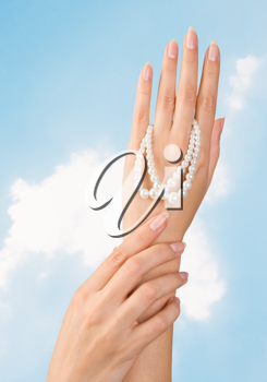 image of beautiful nails and woman fingers with pearls