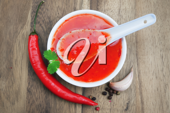 red hot chilli sauce over wooden background