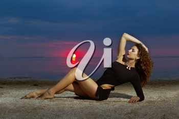Attractive young woman lying on the shore at sunset