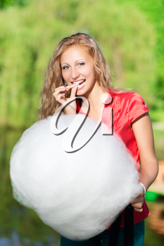 Joyful blond woman posing with a cotton candy outdoors