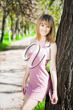 Sexy young woman wearing frank pink dress posing in the park