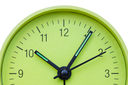 Closeup of hands on green clock face over a white background
