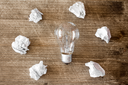 New idea concept with lightbulb and crumpled office paper