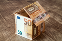 House made of fifty Euro banknotes on a wooden background