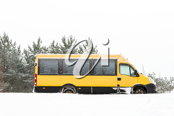 School bus covered with fresh snow. Minibus under the snow. Sleet slush, ice covering on the roads.