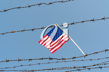 American flag on old barbed wire fence with blue sky background. Borders protection,social issues on refugees or illegal immigrants