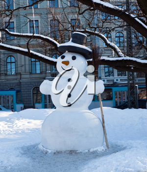 Snowman in the city under the trees