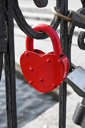 Red padlock on a heart-shaped close-up on the fence on the background of other castles, water, concrete fences