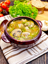 Soup with meatballs, noodles and champignon in a clay bowl on a napkin, parsley, tomatoes, mushrooms and bread on dark background wooden plank