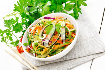Spicy salad of cucumbers, carrots, chili peppers, purple onions, cilantro and black sesame seeds, seasoned with vinegar and lemon juice in a bowl on a napkin on wooden board background