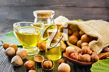 Hazelnut oil in a glass bottle, jar and gravy boat, flour in a bowl, nuts in bag, spoon and on the table, filbert sprigs with green leaves on wooden board background