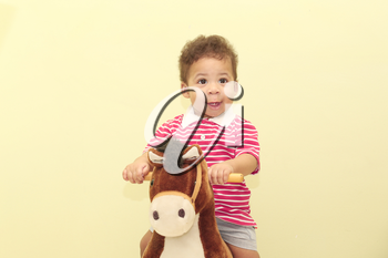 Portrait of an adorable african boy in his horse toy.