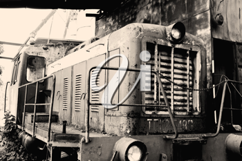 Old rusty locomotive standing on rails, closeup image, sepia