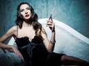 Attractive young woman lying on a sofa and smoking cigarette. Retro style