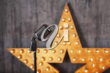 Vintage microphone in studio with star on background