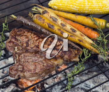 T bone steak cooking on fire with vegetables and herbs