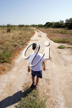 A young child walking on the road
