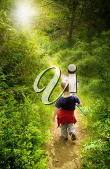 Two young children walking in forest