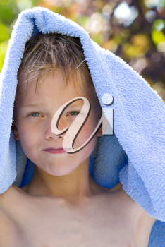 A young child in nature with towel
