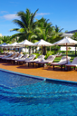 tropical swimming pool with coconut tree and white umbrella