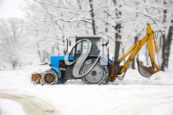 The tractor of dark blue color deletes snow in park