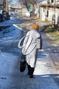 a woman with a bag goes on the road in winter
