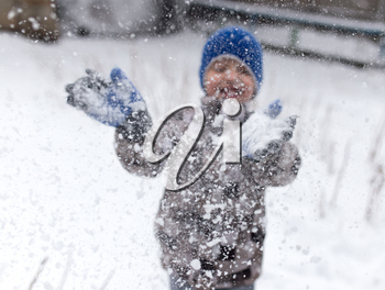 Boy playing with snow on nature in winter