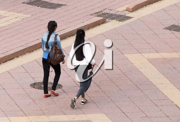 Two girl is walking along paving stones .