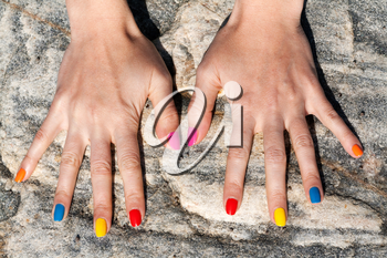 Two female hand with the fashionable color nail polish on the stone