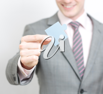 Royalty Free Photo of a Businessman Holding a Puzzle Piece