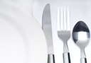 close up of a cutlery set on a table with napkin and dish