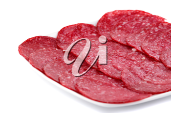 Salami on plate isolated on white background.