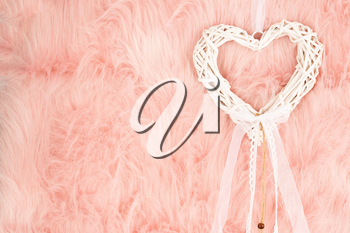 White wooden heart with ribbon on pink fur background.