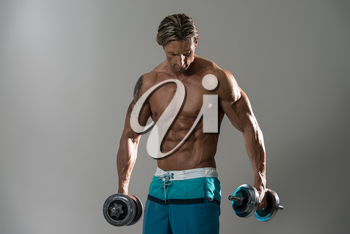 Mature Man Working Out - Dumbbell Concentration Curls On Grey Background