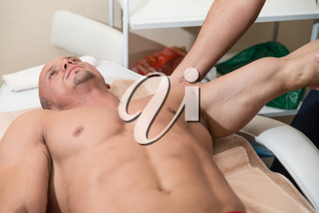 Close Up Of A Handsome Young Man Enjoying His Massage At The Spa Center