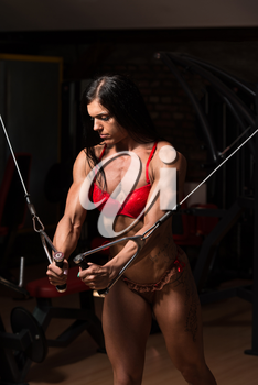 Young Woman In Underwear Is Working On Her Chest With Cable Crossover In A Dark Gym