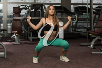 Young Woman Performing Barbell Squats - One Of The Best Bodybuilding Exercise For Legs