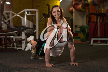 Couple Doing Pushups As Part Of Bodybuilding Training In The Gym