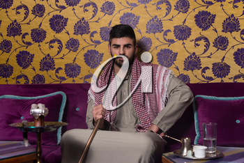 Muslim Man Smoking Turkish Hookah In The Cafe With Colorful Walls On Background
