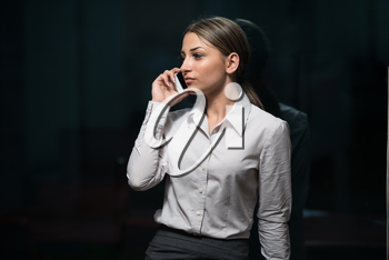 Indoor Portrait Of A Beautiful Happy Brunette Woman Or Businesswoman Talking On Her Cell Phone - City Business Wwoman Working